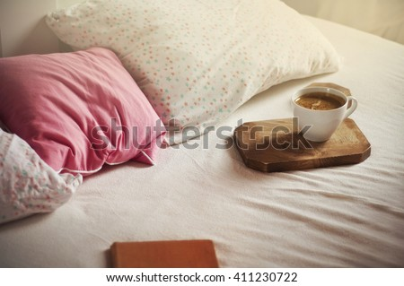 Morning coffee in bed. White coffee cup on wooden board, bed background. Soft pillows - star pattern & pink. Vintage color. Sleepy atmosphere. Place for text. - stock photo