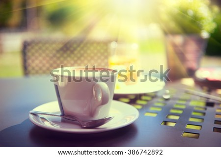 Morning coffee on the terrace. Cup of espresso on the table in sun light, garden view. Breakfast outside - stock photo