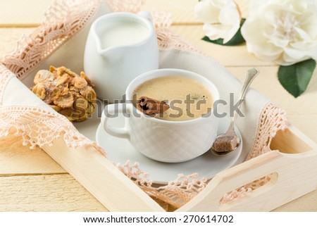 Morning coffee with cinnamon and milk in cream jug on the wooden tray - stock photo