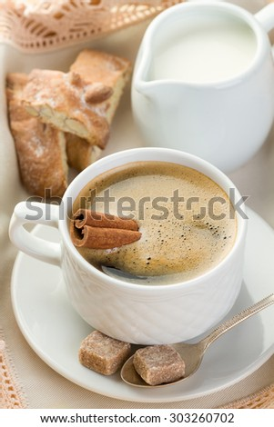 Morning coffee with cinnamon, milk, sugar and nut cookies (vertical shot)