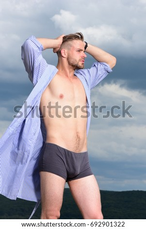 Morning concept. Adult handsome man in fashionable bathrobe. Male model posing against the sky. Sexy young macho on the sky. Bearded attractive guy enjoy healthy morning.