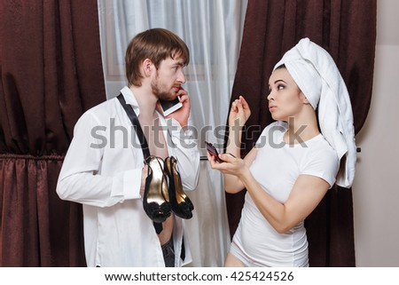 Morning couples. Husband and wife are going to the party. Man talking on the phone and holding her shoes. Girl doing make-up with a towel on her head. Family time. - stock photo