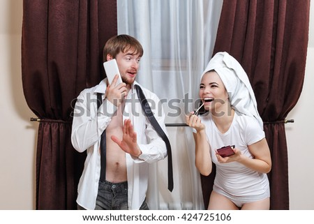 Morning couples. Husband and wife are going to work. Man talking on the phone. Girl doing make-up with a towel on her head. Girl laughs. - stock photo