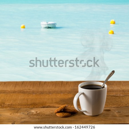 Morning cup of coffee on a wooden picnic table on St Martin in Caribbean in idyllic dreamlike location with a power boat moored just off the deck - stock photo