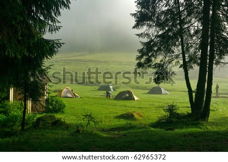 Morning dew and tents in the mountain camp site - stock photo