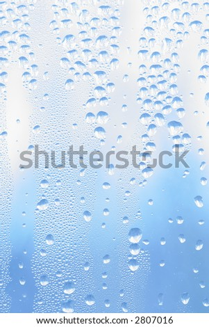 Morning dew droplets on window with backyard tree branches reflected, morning light blue sky - stock photo