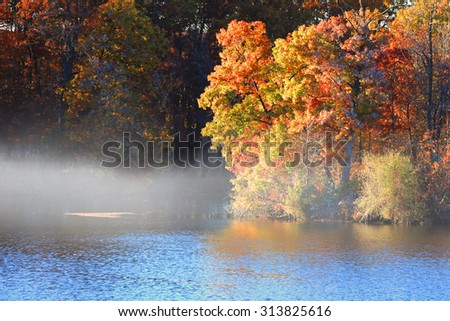 Morning fog on the lake in autumn time - stock photo
