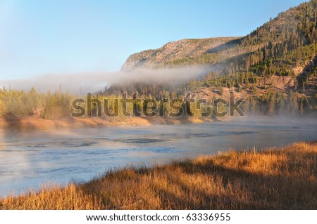 Morning fog on the Madison River in Yellowstone National Park, Wyoming. - stock photo