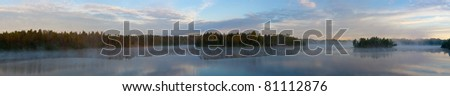 Morning fog over wood lake, a panorama - stock photo