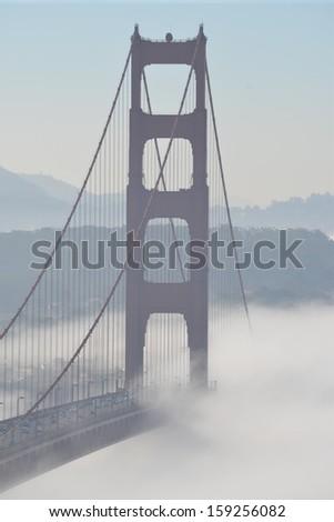 Morning fog passing under the Golden Gate Bridge - stock photo