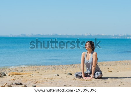 Morning gymnastics and yoga. Young beautiful woman or girl has a workout on the beach by the sea. Summer weather on the ocean adorns sports enthusiasm sexual girl. Skinny woman exercising outdoors