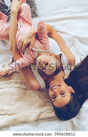 Morning hugs. Top view of cheerful beautiful young woman looking at camera with smile and hugging her baby girl while lying in bed  - stock photo