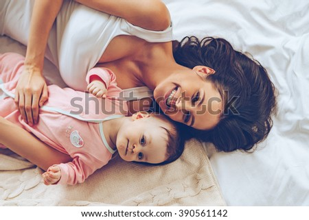 Morning hugs. Top view of cheerful beautiful young woman looking at camera with smile while lying in bed with her baby girl - stock photo