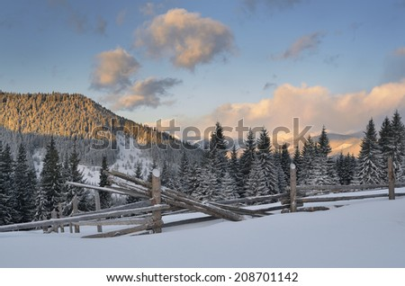 Morning in the mountains. Winter landscape with coniferous forest and wooden fence - stock photo