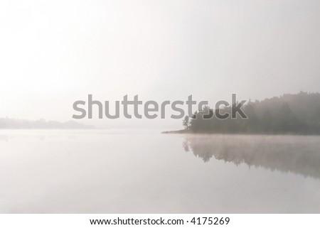 Morning lake in a fog - stock photo