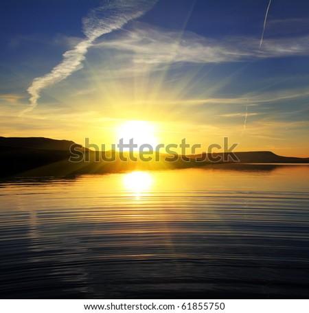 morning lake landscape with sunrise over mountains - stock photo