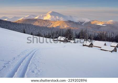 Morning landscape in the mountains. Ski tracks in the snow. Wooden houses in the village of shepherds. Carpathians, Ukraine - stock photo
