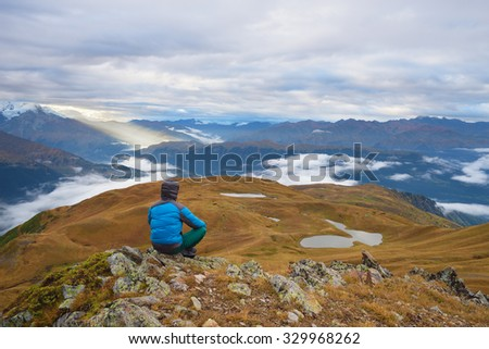 Morning landscape. Tourist in the mountains sits on a rock and looking over the valley. Overcast. Lake Koruldi. Main Caucasian ridge. Zemo Svaneti, Georgia
