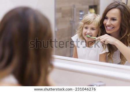 Morning lesson of brushing teeth with mommy  - stock photo