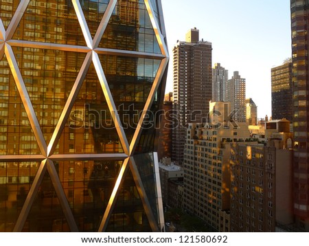 Morning light on a glass and steel building with a brownstone reflected in it's reflective glass in New York City and Manhattan - stock photo