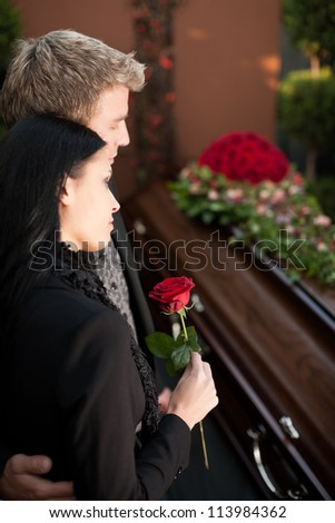 Morning man and woman on funeral with red rose standing at casket or coffin - stock photo