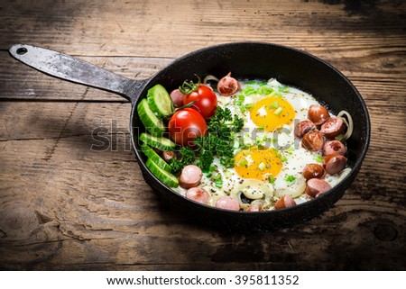 Morning meal- two fried eggs with sausages and fresh vegetables in old pan - stock photo