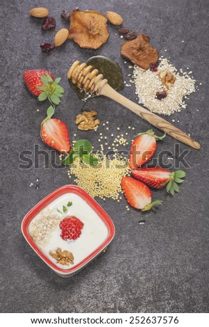 Morning meals. Strawberries and cream oatmeal ingredients. Healthy breakfast with yogurt, strawberries, oat flakes, nuts and honey. Macro, selective focus - stock photo
