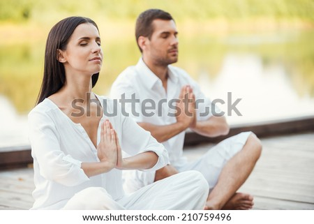 Morning meditation. Beautiful young couple in white clothing meditating outdoors together and keeping eyes closed - stock photo