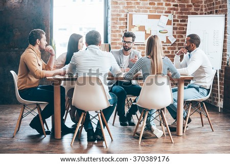 Morning meeting. Group of six young people discussing something while sitting at the table in office together - stock photo