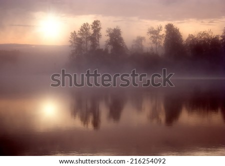 Morning nature scene (landscape): the sun in fog (mist) reflected on the water surface along with opposite shore and trees. The Seliger lake (Russia). Can be used as a background or wallpaper. - stock photo