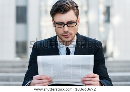 Morning news. A young businessman reading a newspaper outdoors - stock photo