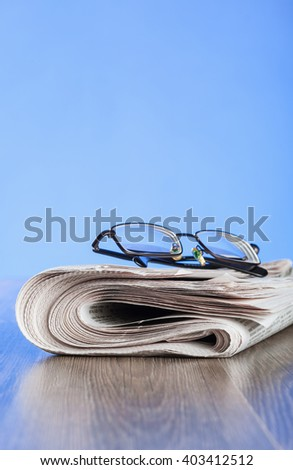 Morning newspaper and glasses on the table, closeup shot