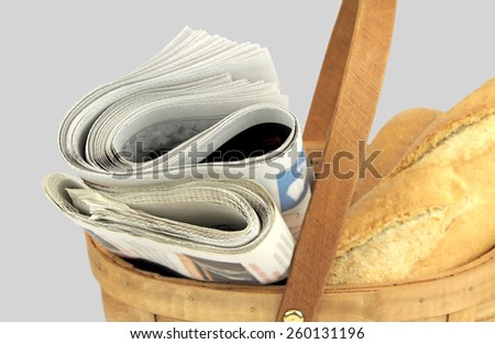 Morning newspapers and fresh bread in basket - stock photo
