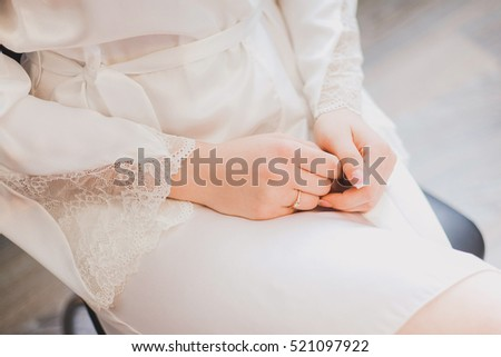 Morning of young beautiful woman sitting on chair with her hands crossed. Female fingernails with classic pink french manicure. Getting ready for wedding ceremony. Horizontal color image