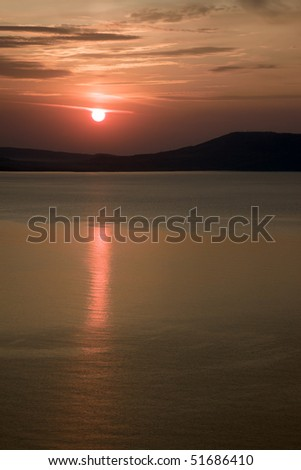 Morning on sea coast, red sun is reflected in water
