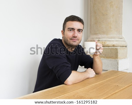 morning portrait of a guy holding coffee cup. - stock photo