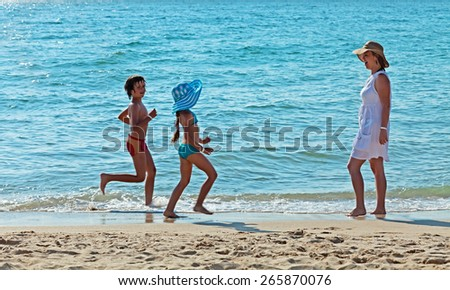 Morning run by the sea - kids and their mother exercising for fun - stock photo