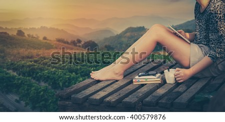 Morning scene of young woman holding coffee cup by right hand and holding small tablet pc while sitting on wood litter on weekend with mountain view in blurry background, processed with vintage effect - stock photo