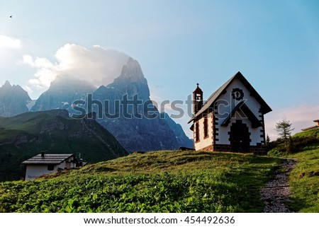 Morning scenery of a lovely church at the foothills of rugged mountain peaks ( Cimon della Pala ) under dramatic dawning sky in Passo Rolle, Dolomiti, Trentino Alto Adige, South Tyrol, Italy, Europe - stock photo