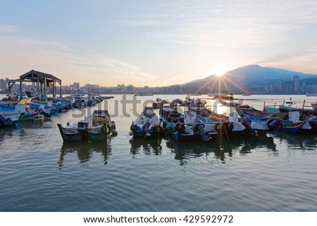 Morning scenery of Tamsui River at sunrise in Taipei Taiwan, with a view of fishing boats parking on peaceful water by the riverside & Yangmingshan Mountain under beautiful dawning sky in background - stock photo