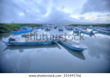 Morning scenery of Tamsui River in Taipei Taiwan, with stranded boats on still water during a low tide under gloomy cloudy sky  - stock photo