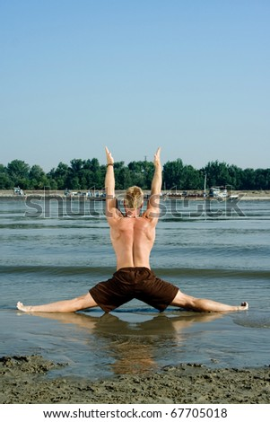 morning stretching and warming up on the beach.Healthy lifestyle - stock photo