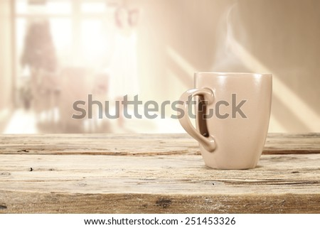 morning sun in window and mug of coffee and desk of wood  - stock photo