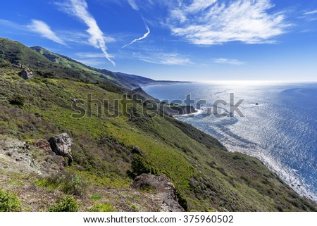 Morning sunrise, beautiful shimmering blue sea & sky, aquamarine waters, jet contrails,  steep sheer jagged cliffs, traveling the Big Sur Highway, on the California Central Coast, near Cambria CA. - stock photo