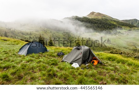 Morning sunrise in mountains with camping tent.