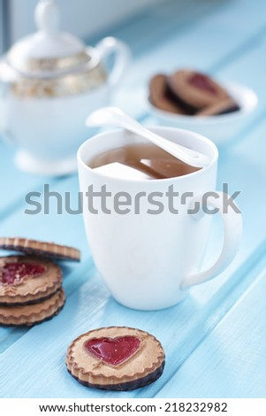 Morning tea cup with sweet cookies on the wooden blue table - stock photo