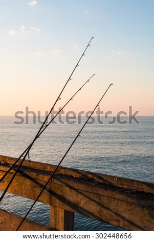 Morning view of fishing poles on pier railing.