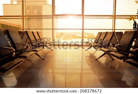 Morning view of international airport indoor hall with glass window. Modern lounge room of airport building with comfortable seats. - stock photo