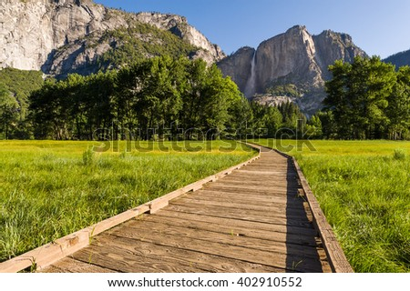 Morning view of Yosemite Falls with wooden boardwalk. - stock photo