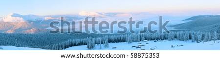Morning winter calm mountain panorama with sheds group and mount ridge behind (Carpathian Mountains, Ukraine).  Nine shots stitch image. - stock photo